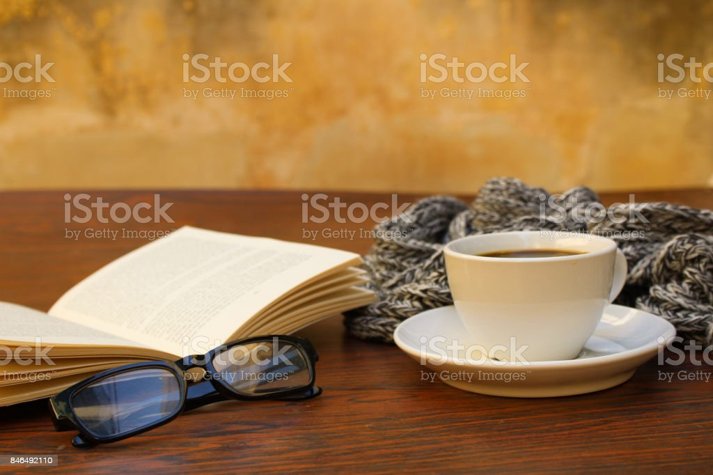 cocoffee cup, glassess book and scarf on wooden table stock photo