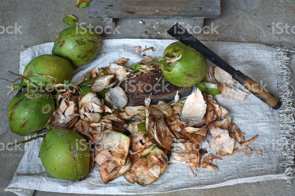 ココナッツとココナッツ シェル コンクリート背景にナイフと小さな椅子をチョッピング - オーガニックのロイヤリティフリーストックフォト