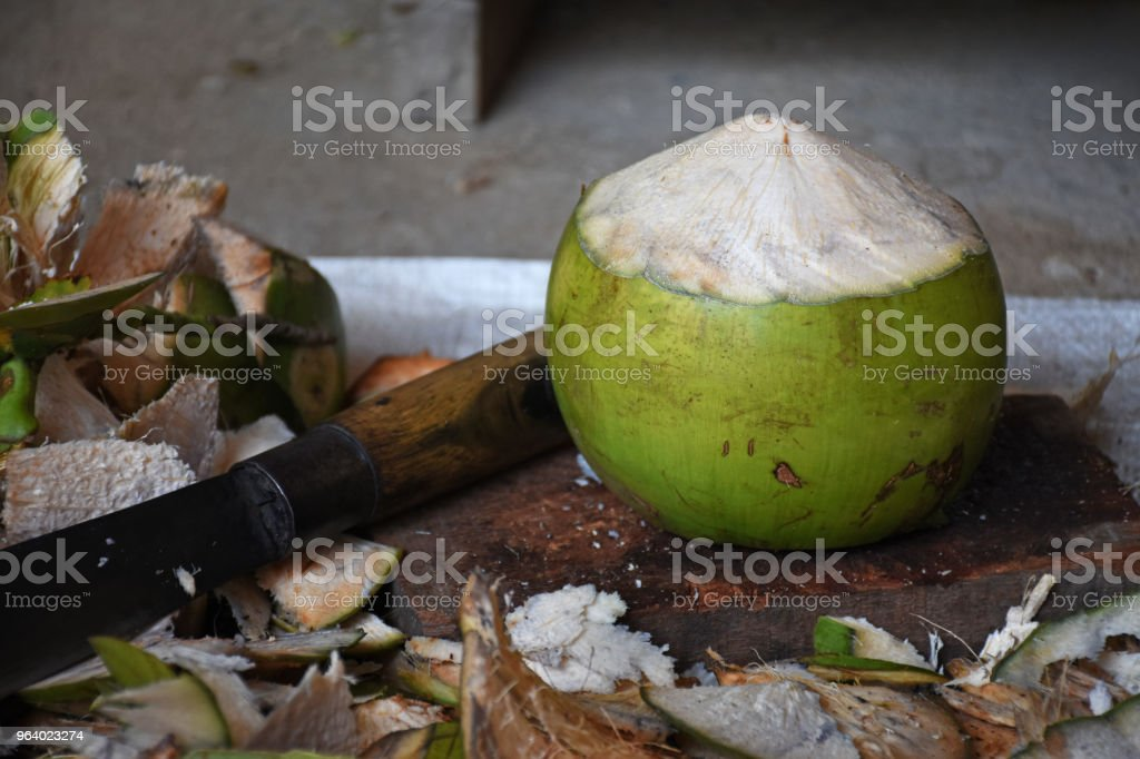 Coconut and coconut shell with chopping knife on concrete background - Royalty-free Abstract Stock Photo