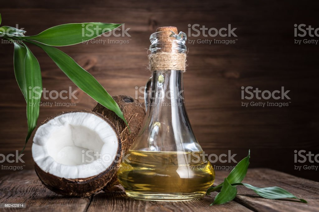 coconut and oil on a wooden background stock photo