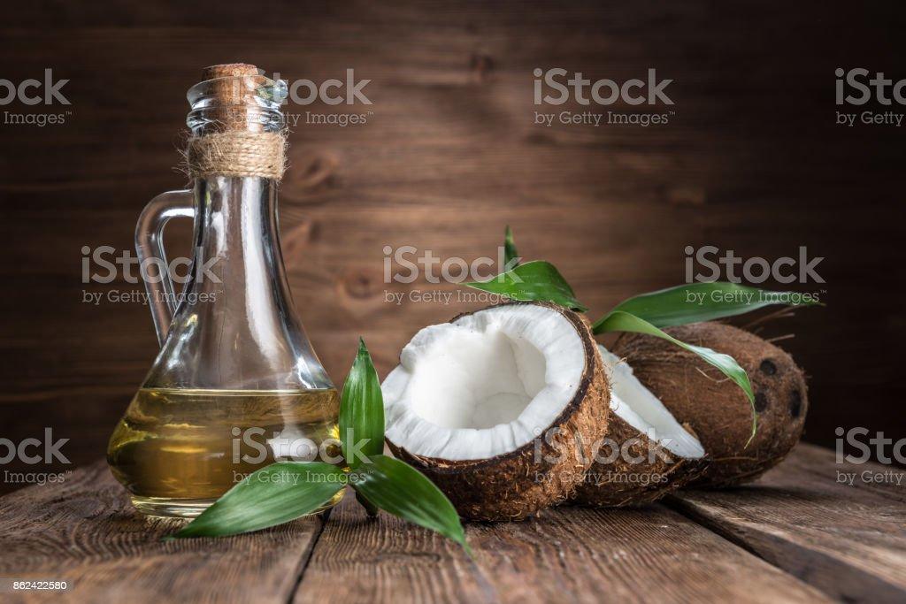 noix de coco et l'huile sur un fond en bois - Photo