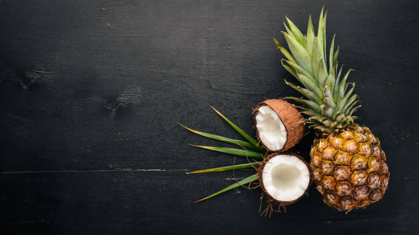 Coco e abacaxi em um fundo de madeira. Nozes e frutas tropicais. Vista superior. Espaço livre para texto. - foto de acervo