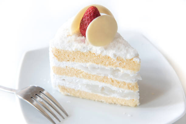 coconut cake topping strawberry on white plate. - кусок торта стоковые фото и изображения