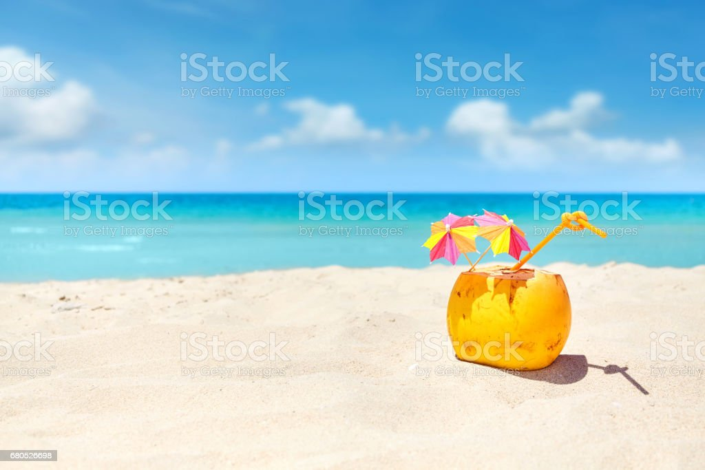 Coconut cocktail with straw and colorful umbrellas on a beach. stock photo