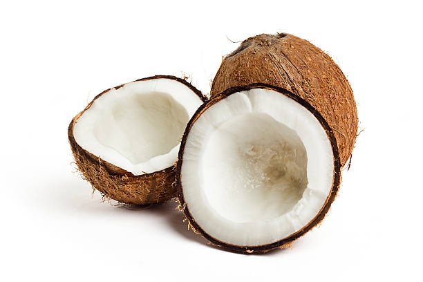 Coconut cracked open with a whole coconut on white back stock photo