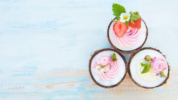 kokos-muffins mit blumen, erdbeeren und käse-sahne. ansicht von oben, textfreiraum - 3 zutaten kuchen stock-fotos und bilder