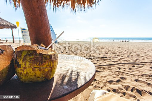 Coconut drinks on a table with a beach view.