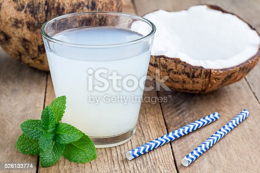 Coconut drink with pulp in glass on wooden table