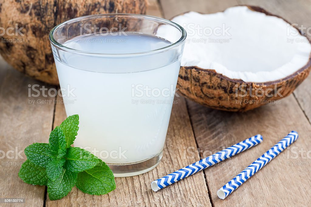 Coconut drink with pulp in glass on wooden table stock photo