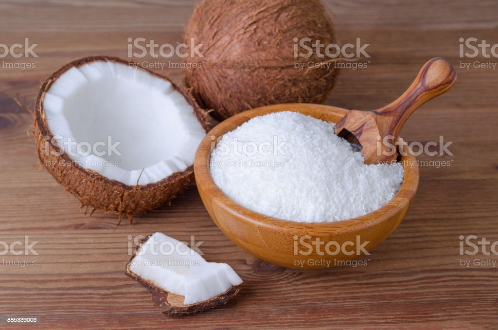 coconut flakes in a bowl on wooden background stock photo