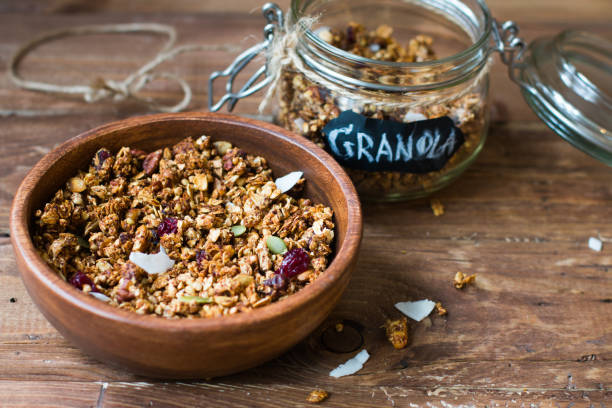coconut granola in wooden bowl and glass jar on wooden background - granola imagens e fotografias de stock