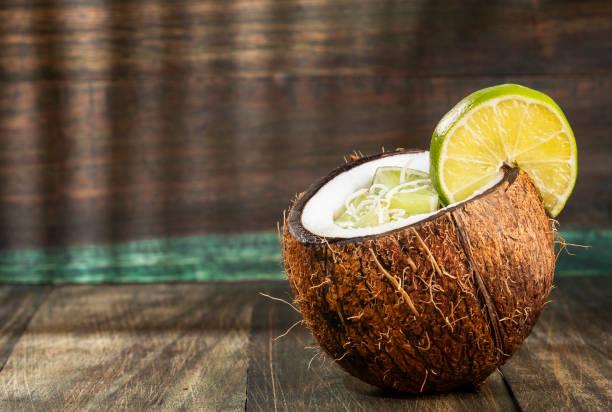 limon ile hindistan cevizi suyu-cocos nucifera - hindistan cevizi tropik meyve stok fotoğraflar ve resimler