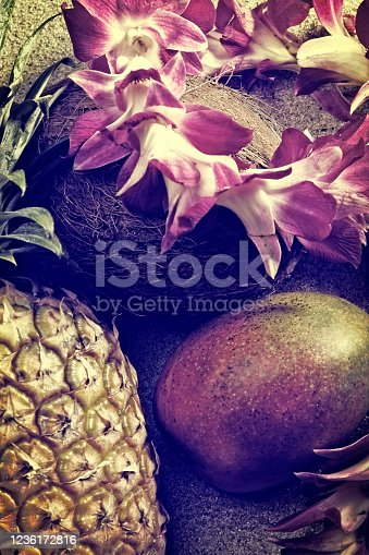 This is a close up photo of a mango, pineapple, coconut and lei on a sandy beach
