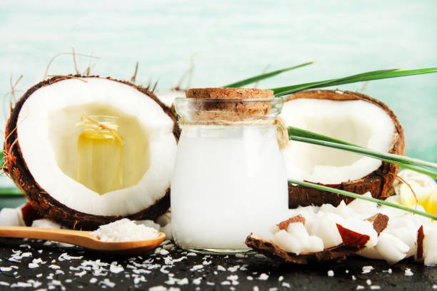 Coconut milk glass jar with nuts and oil bottles, fresh coconut flakes. stock photo