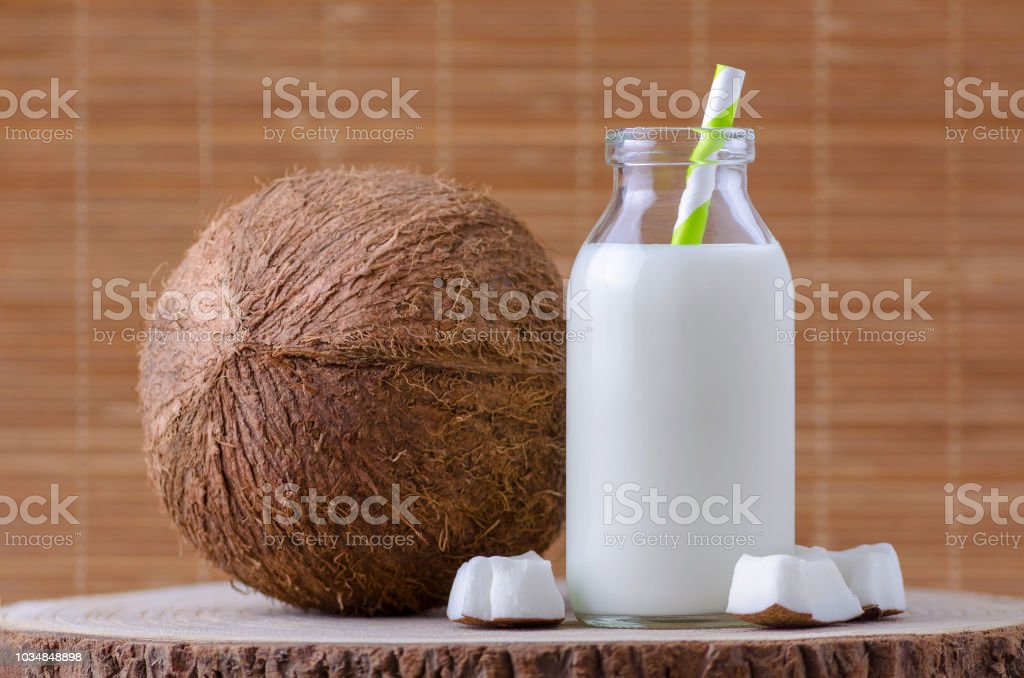 coconut milk in glass bottle with tubule on natural wooden brown background stock photo