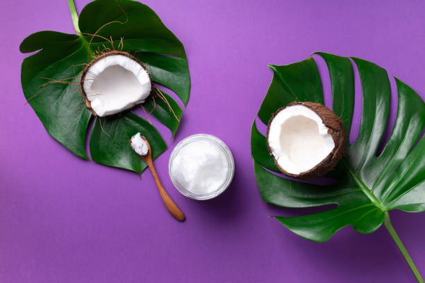 Coconut oil and ripe coconuts, tropical palm and monstera leaves on violet background with copy space. Top view. Summer creative layout. Coconut oil and ripe coconuts, tropical palm and monstera leaves on violet background with copy space. Top view. Summer creative layout coconut oil stock pictures, royalty-free photos & images