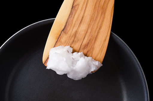 istock Coconut oil on wooden spatula over coated pan 613241666
