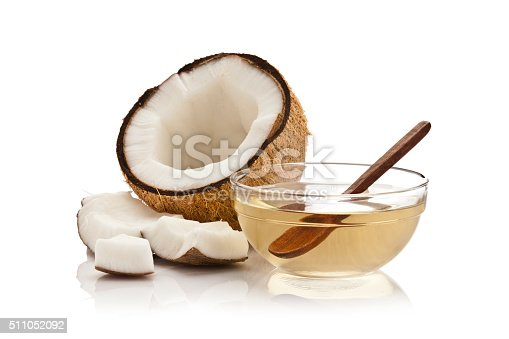 Glass bowl filled with coconut oil and half coconut with pieces isolated on white background