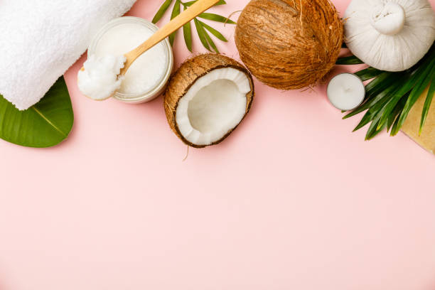 Coconut oil, tropical leaves and fresh coconuts stock photo