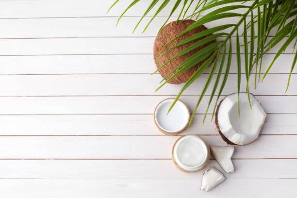 Kokosöl mit frischem Kokosnuss, Naturkosmetik, flaches Laienbild auf Holzhintergrund – Foto