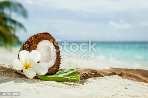 Fresh Coconunt cut in halves with flower and leaves in the sand.