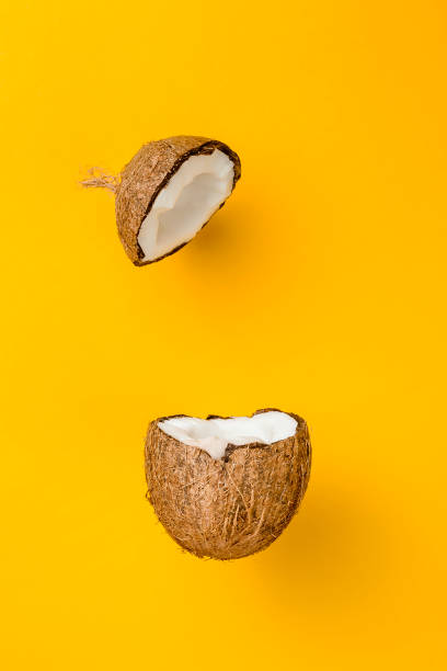 Coconut on yellow colored background, minimal flat lay style stock photo