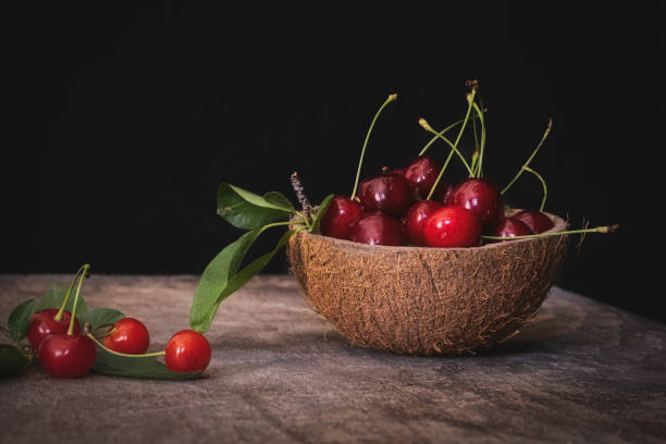 Coconut shell bowl full of fresh cherries in the shell on a wooden table on black background stock photo