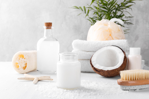 Spa setting and health care items, coconut body oil,lotion, sponge, bath salt and towels, white table