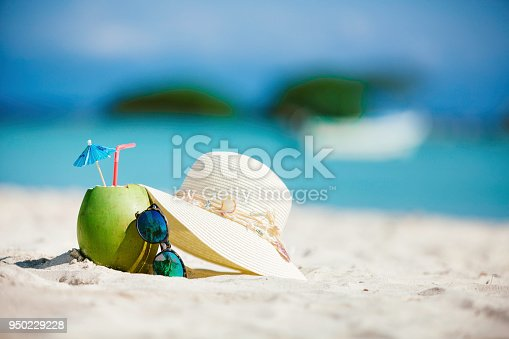 Coconut tropical drink with sunglasses and female hat on sand in a Caribbean island turquoise beach