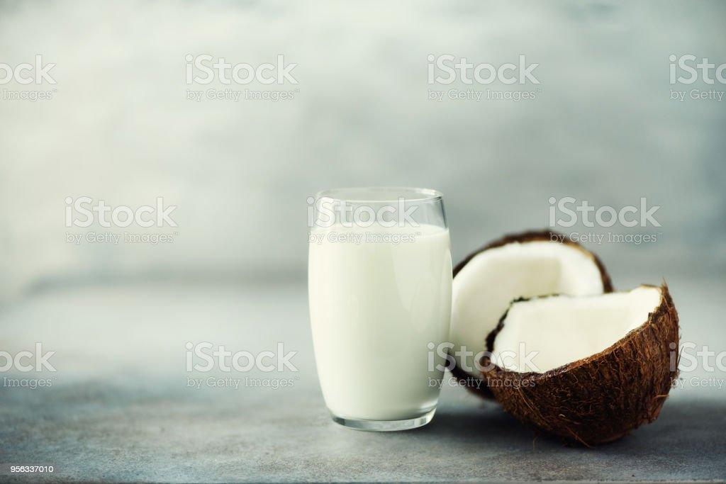 Coconut vegan milk non dairy in glass and coconut fuit halves on grey concrete background with copy space. Vegetarian eating concept stock photo