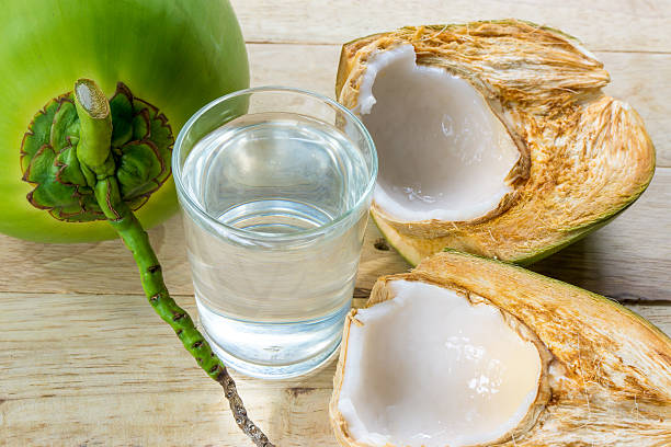 coconut water and fresh coconut on wooden background - foto de acervo