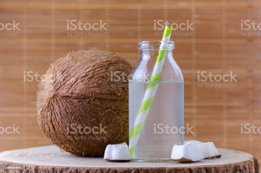 coconut water in a glass jar with tubule and coconut on natural background stock photo