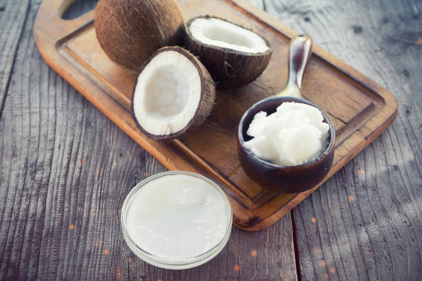 Coconut with coconut oil in jar on wooden background stock photo