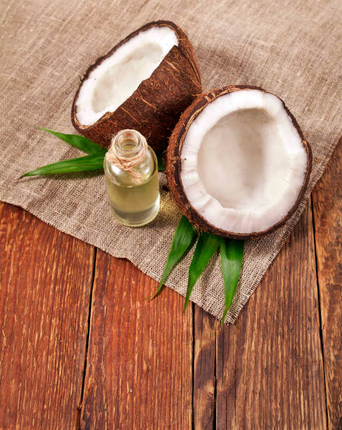 Coconut with coconut oil Coconut on palm leaves with melted coconut oil in a glass bottle on wooden background. coconut oil stock pictures, royalty-free photos & images