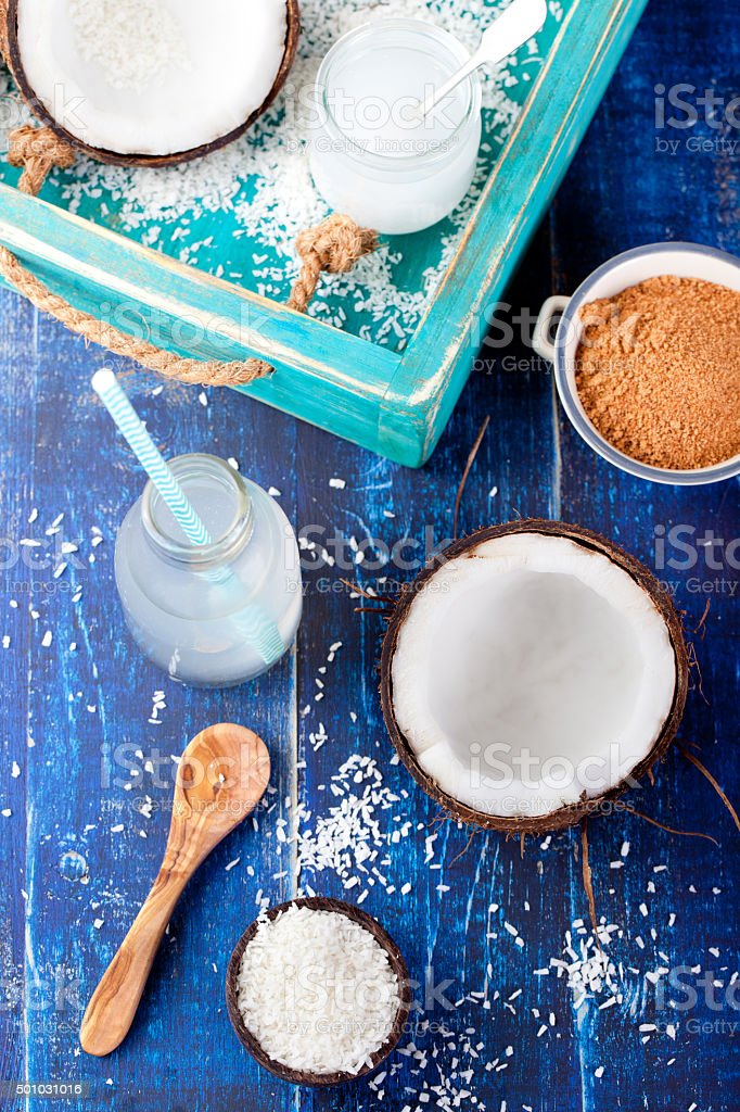 Coconut with coconut oil, water, sugar and flakes stock photo