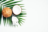 Coconut with palm leaf on white background. Flat lay, top view. Summer background with natural organic food