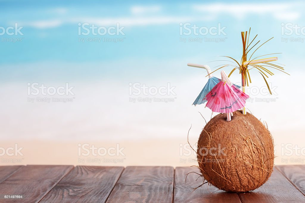 Coconut with straw parasols on table in front sea. photo libre de droits