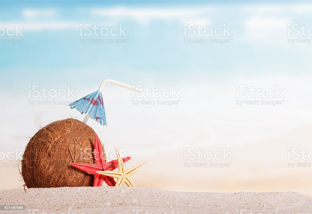 Coconut with straw, umbrella and starfish in sand against sea. foto stock royalty-free