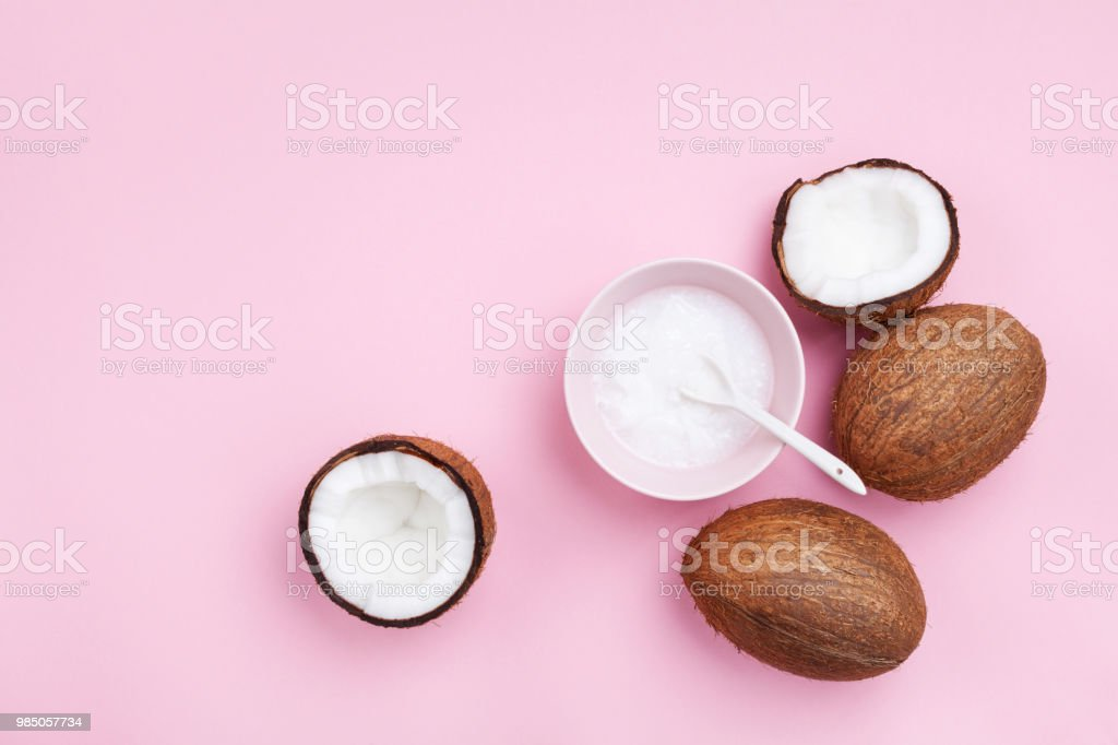 Coconuts fruit with coconut oil on pink pastel table top view. Beauty and spa organic cosmetic. Flat lay. stock photo