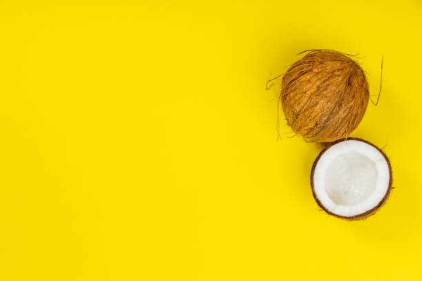 Coconuts on yellow background stock photo