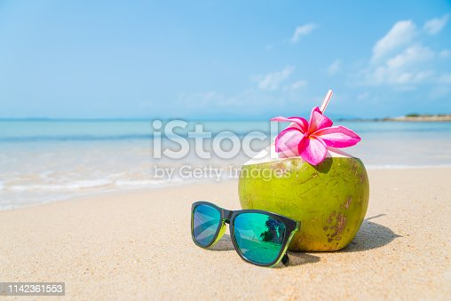 Coconuts with drinking straw and sunglasses on the tropical beach.