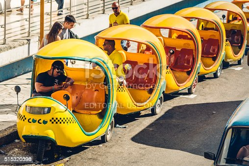 Havana, Cuba - March 18, 2015: Coco-taxis parked at a street of Havana, driver waiting for clients. The three wheeled vehicle  is a common form of public transportation in the city of Havana Cuba.
