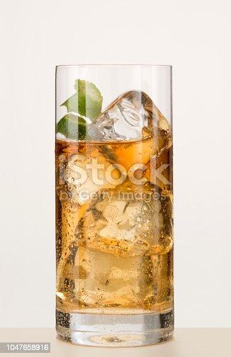 vaso largo con licor, hielo y cascara de limon, sobre fondo blanco
