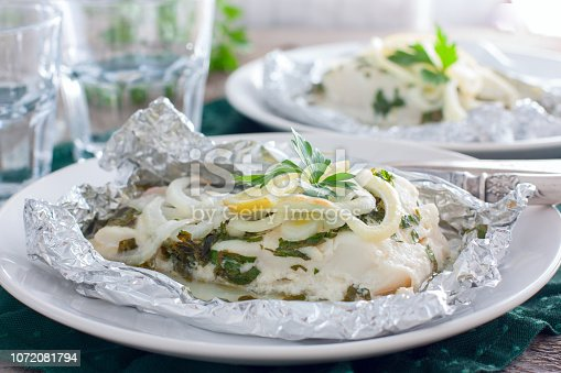 istock Cod baked in foil with parsley and onion, horizontal 1072081794