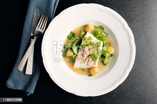 Overhead dish of cod fillet in a beurre blanc sauce with apple balls, and sugar salted apple chips, parsley and watercress at the pass before serving. Colour, horizontal  with some copy space, photographed on location at a restaurant on the island of Moen in Denmark.
