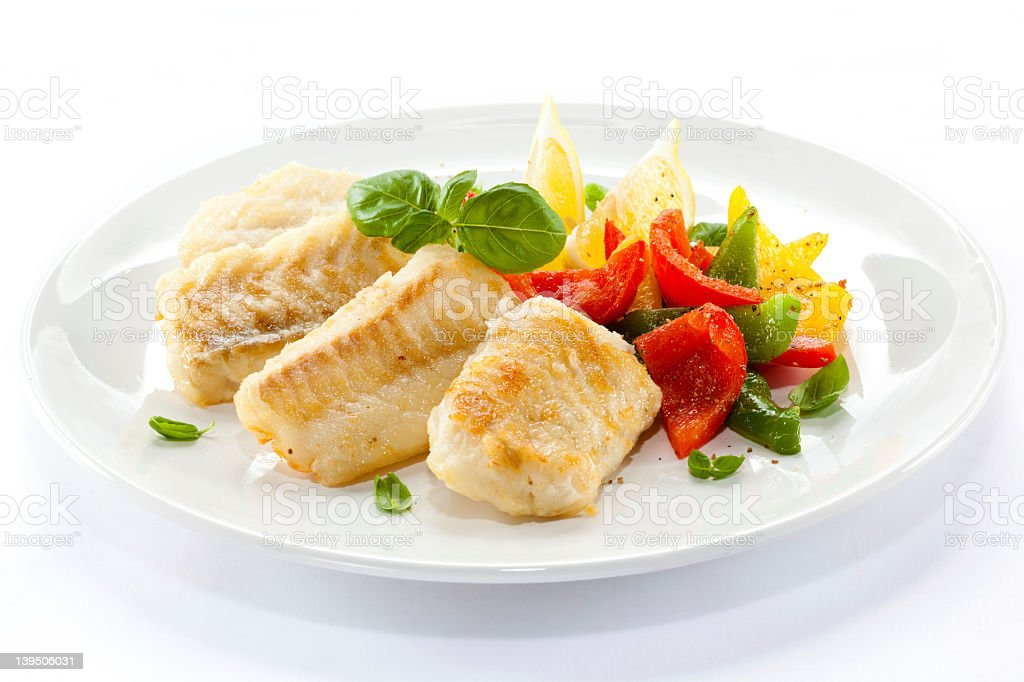 Cod fillets and cooked vegetables on a white plate stock photo
