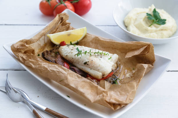 Cod fillets baked in parchment paper with vegetables stock photo