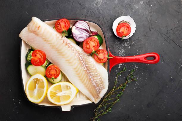 cod. frische seeluft weiße roher fisch vor dem kochen in einer pfanne mit frischem gemüse: zucchini, süßen zwiebeln, tomaten und zitronen. ansicht von oben. food-konzept - heilbutt stock-fotos und bilder