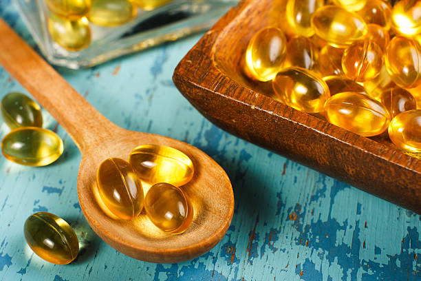 cod liver oil capsules - cod liver oil stock photos and pictures