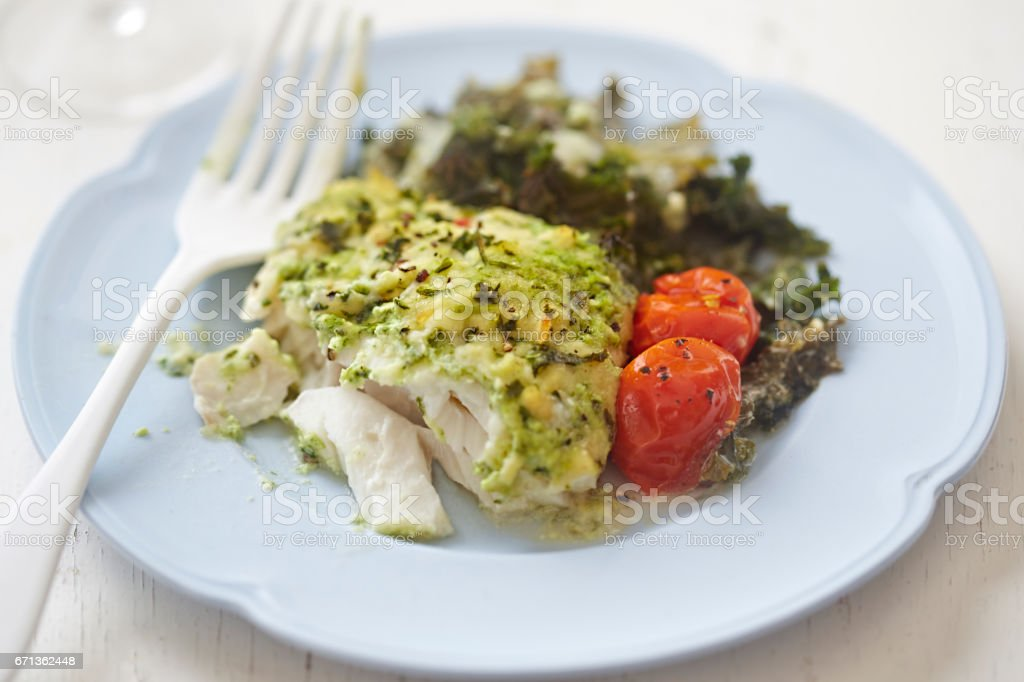 Cod with parsley crumb kale and cherry tomatoes stock photo